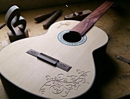 Guitarra personalizada con tallados en la tapa.