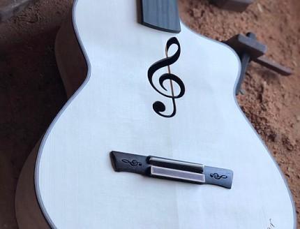 Guitarra con Clave de Sol y nombre tallados en la madera.